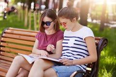 Fundersamma två flickor bär tillfällig kläder, sitter på träbänk parkerar och talar in om nyheterna som beskrivas i den senaste t royaltyfri bild