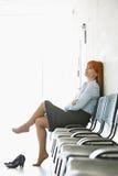 Fundersamt affärskvinnasammanträde med ben korsade på stol i regeringsställning Royaltyfri Foto