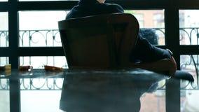 Fundersamt affärsmansammanträde på en stol vid fönstret