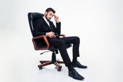 Fundersamt attraktivt businessmansitting i regeringsställning stol och genom att använda mobiltelefonen royaltyfria foton