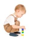 Fundersamt barn som spelar med isolerade leksaker Arkivbild