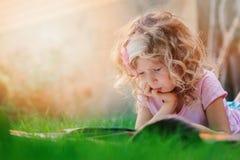 Fundersamt barnflickalära och läsebok på sommarsemester i trädgården Royaltyfri Fotografi