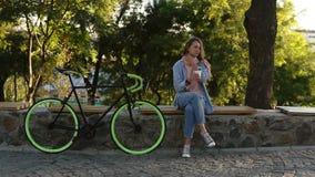 Fundersamt flickasammanträde på bänken i staden parkerar med hennes trekking cykel bredvid henne Se hennes mobil som bär lager videofilmer