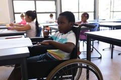 Fundersamt inaktivera skolpojken som bort ser på skrivbordet i klassrum arkivfoto