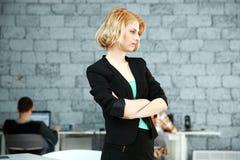 Fundersamt kvinnaanseende med vikta armar Arkivfoton