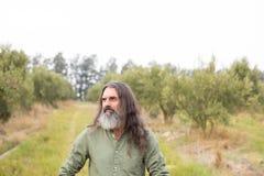 Fundersamt mananseende i olivgrönt fält Fotografering för Bildbyråer