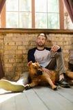 Fundersamt mansammanträde på golv med hans hund som rymmer telefonen i hand Royaltyfri Foto