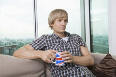 Fundersamt mitt--vuxen människa mansammanträde med kaffekoppen i vardagsrum hemma Arkivfoto
