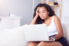 Fundersamt sammanträde för ung kvinna på soffan arkivfoton