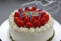 Fundindo para fora velas no bolo de aniversário Foto de Stock