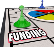 Funding Financial Backing Investment Money Resources Board Game. Funding word on a board game and a winning piece moving forward to secure financing for a Stock Photos