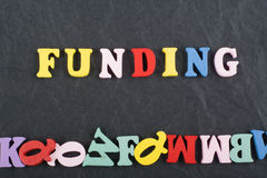 FUNDING word on black board background composed from colorful abc alphabet block wooden letters, copy space for ad text Royalty Free Stock Photos