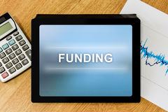 Funding word on digital tablet. With calculator and financial graph Royalty Free Stock Photography