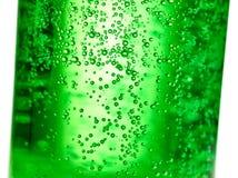 Fundo abstrato: bolha da soda da água gasosa na garrafa de vidro verde com luz do inclinação imagens de stock royalty free