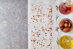 Fundo abstrato cinzento com espaço para o texto Frasco do azeite, frasco do vinagre da videira, bacia com azeitonas em um pano br Foto de Stock
