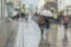 Fundo abstrato de dois jovens sob o guarda-chuva, caminhada na estrada na cidade na chuva Gotas da água no vidro intencional Imagem de Stock Royalty Free