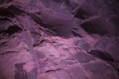 Fundo abstrato de uma parede de pedra em uma luz roxa cor-de-rosa Fotografia de Stock Royalty Free