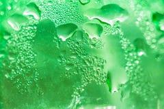 Fundo abstrato feito de cubos de gelo em um close up verde plástico da garrafa Foto de Stock Royalty Free