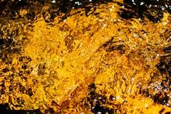 Fundo abstrato obscuro amarelo dourado outonal da água Formado das reflexões ensolaradas de árvores e de movimento de floresta em Foto de Stock Royalty Free