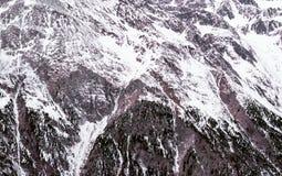 Fundo alpino do inverno O terreno montanhoso na neve fotografia de stock royalty free