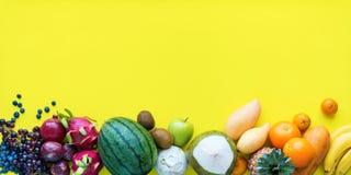 Fundo amarelo ajustado dos frutos tropicais de vista superior foto de stock