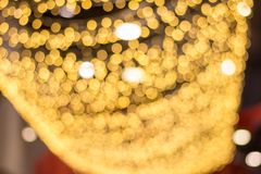 Fundo amarelo do bokeh do borrão do sumário da luz de suspensão da decoração no armazém fotos de stock royalty free