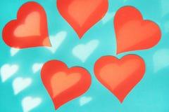 Fundo azul com cora??es vermelhos Efeito da luz da m?scara do Gobo na forma de um cora??o foto de stock royalty free