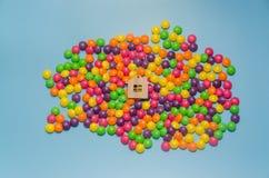 Fundo azul com doces e a casa de madeira do brinquedo imagem de stock