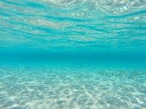 Fundo azul subaquático do oceano com parte inferior de mar arenosa imagem de stock royalty free