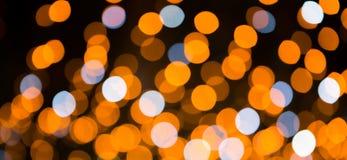 Fundo bonito do feriado com luzes amarelas, alaranjadas e azuis brilhantes do bokeh Textura festiva Luzes de Natal Colorido borra foto de stock