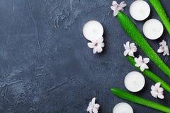Fundo bonito dos termas com folhas, as flores e velas verdes na tabela de pedra preta de cima de Aromaterapia e beleza Foto de Stock