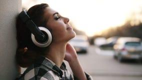 Fundo borrado brilhante fora Opinião lateral uma menina bonita que põe sobre fones de ouvido e que relaxa Escute filme