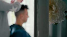 Fundo borrado: homem no barbeiro O cabeleireiro faz o corte de cabelo com tesouras filme