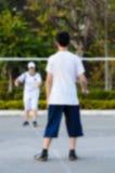 Fundo borrado: menino e menina que jogam o badminton Imagens de Stock