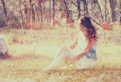 Fundo borrado surreal da jovem mulher que senta-se na pedra no conceito abstrato e sonhador da floresta a imagem é textured e ret Imagens de Stock