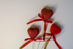 Fundo branco congratulation St Dia do ` s do Valentim Corações vermelhos nas lantejoulas e com curvas Uma decoração para a casa A fotografia de stock