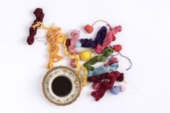 Fundo branco da xícara de café com as bolas coloridas de lãs Fotografia de Stock