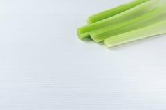 Fundo branco e verde lateral de canto com aipo verde cru Imagens de Stock Royalty Free
