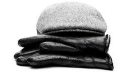 Fundo cinzento do branco das luvas de couro do preto do tampão da mistura de lã Fotografia de Stock Royalty Free
