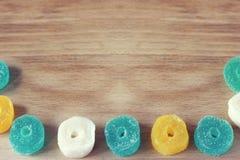 Fundo claro de madeira e doce de fruta multi-colorido ao longo do contorno Adoce doces doces do Natal Doce gelatinoso diferente imagens de stock