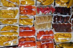 Fundo colorido com os frutos envolvidos no celofane com a forquilha plástica branca Imagens de Stock Royalty Free