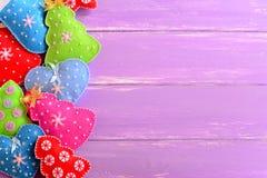 Fundo colorido do Natal Árvores de Natal bonitos de feltro, mitenes, corações, estrelas no fundo de madeira lilás com espaço vazi Imagem de Stock
