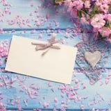Fundo com as flores cor-de-rosa de sakura e Empty tag na madeira azul Fotos de Stock Royalty Free