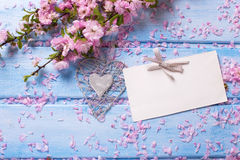 Fundo com as flores cor-de-rosa de sakura e Empty tag na madeira azul Fotografia de Stock Royalty Free