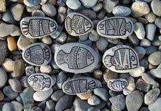 Fundo com as pedras com os peixes pintados da decoração Imagens de Stock