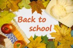 Fundo com lenço e tampão feitos malha, com folhas de outono e maçãs e inscrição DE VOLTA À ESCOLA Fotos de Stock Royalty Free
