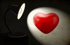 Fundo com a lâmpada e o coração de mesa da iluminação Fotografia de Stock