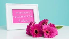 Fundo com o íon cor-de-rosa escuro dos gerberas a tabela e a moldura para retrato branca com mensagem do dia das mulheres felizes Fotografia de Stock Royalty Free
