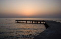 Fundo com o cais de madeira velho no mar no por do sol imagens de stock royalty free