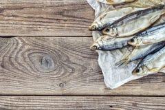 Fundo com os peixes salgados no papel em placas de madeira do grunge pl Imagem de Stock Royalty Free